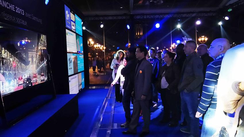 2013 nuit blanche에 전시된 삼성 UHD TV 85에서 재생되는 파리 야경을 보고 있는 방문객들입니다.