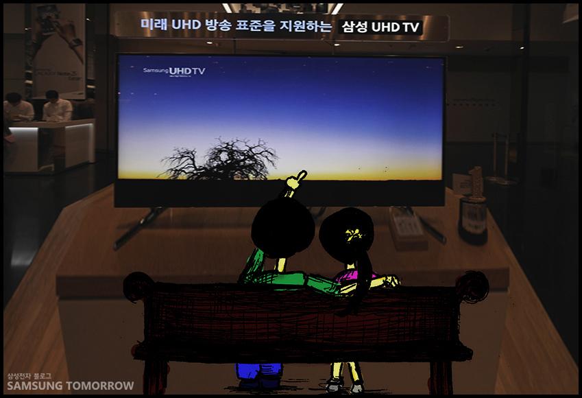 수지와 준수가 삼성 UHD TV를 바라보고 있습니다.