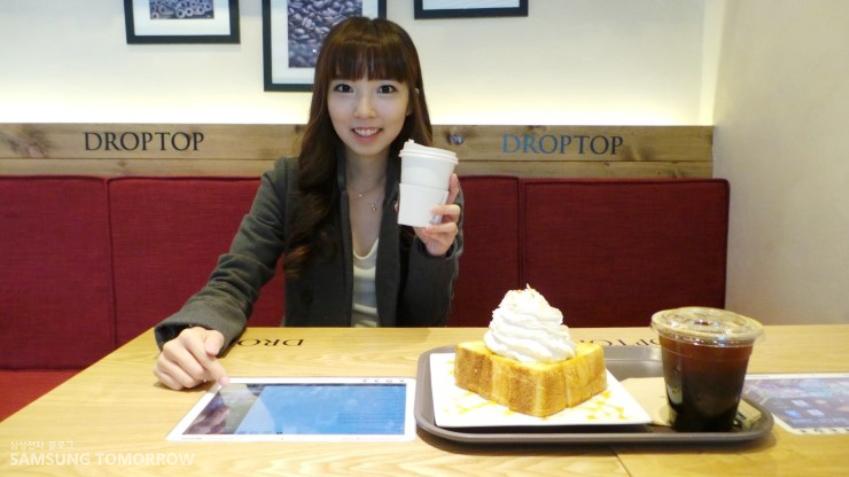 삼성스토리텔러 수경이가 한손에 커피를 들고 다른 손으로는 터치탁을 이용하고 있습니다.