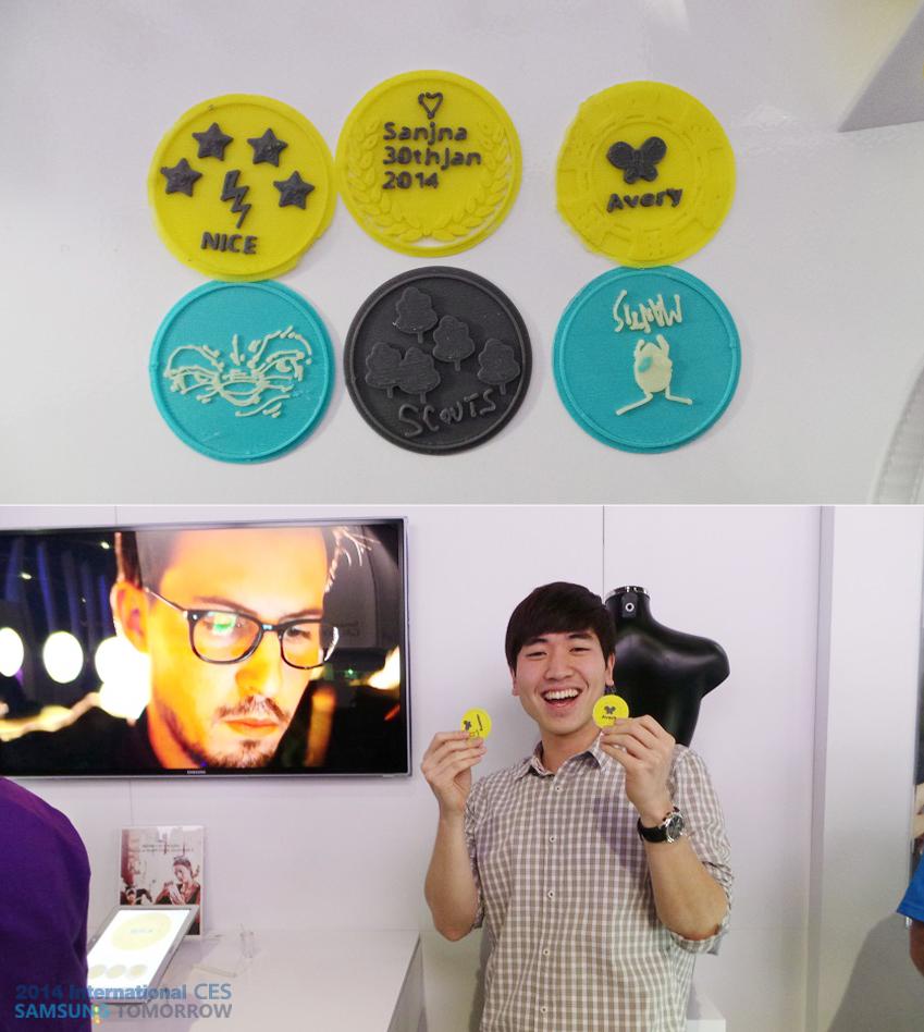 3D 프린팅 앱으로 만든 다양한 스마트폰 케이스 스티커와 선물을 받고 좋아하는 CES 2014 참가자의 모습입니다.
