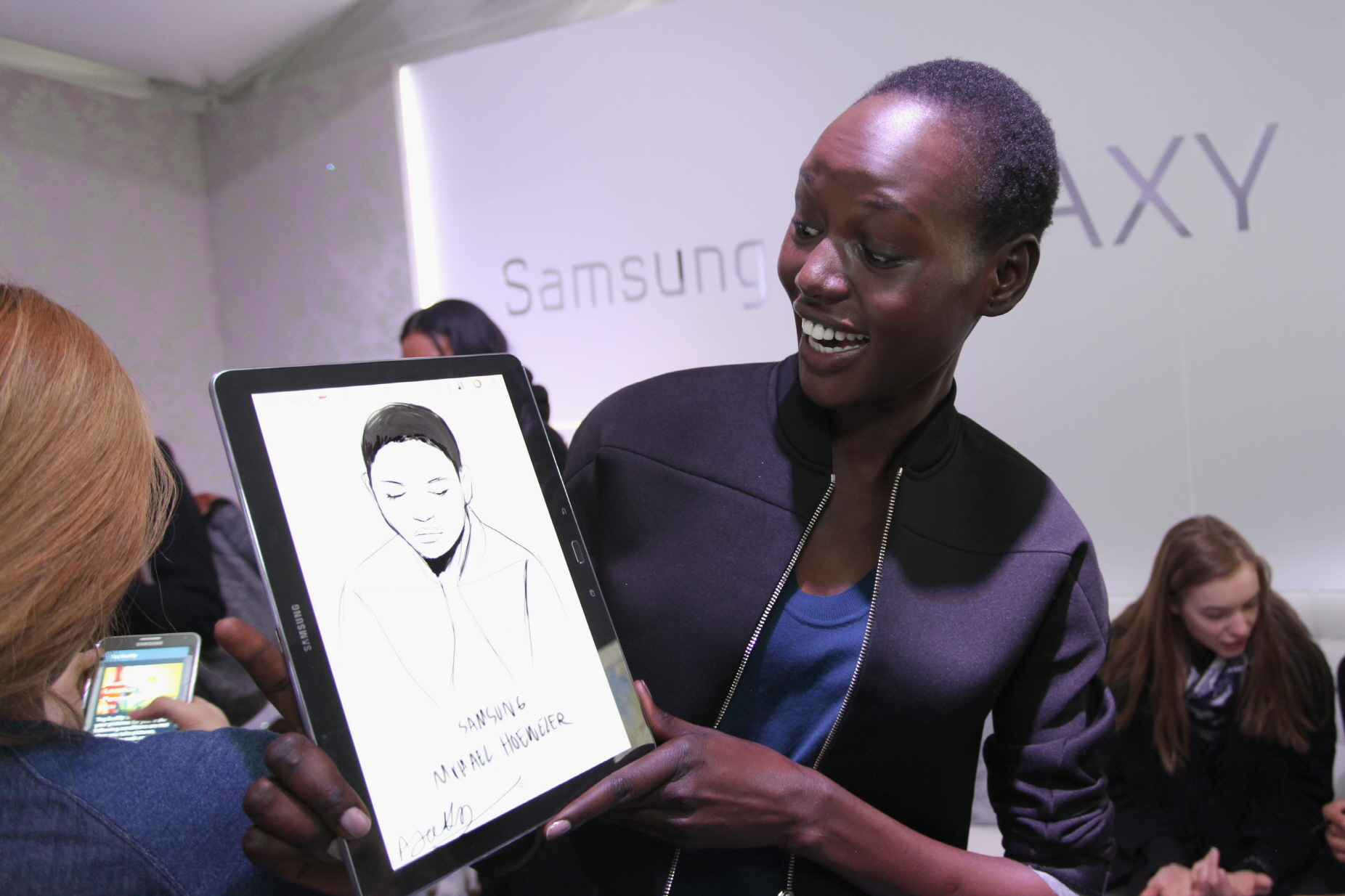 2014년 F/W 뉴욕 패션위크 백스테이지의 '삼성 갤럭시 라운지(Samsung Galaxy Lounge)'에서 자신의 스케치가 그려진 갤럭시 노트 프로와 함께 포즈를 취하고 있는 모델 아작 뎅(Ajak Deng)