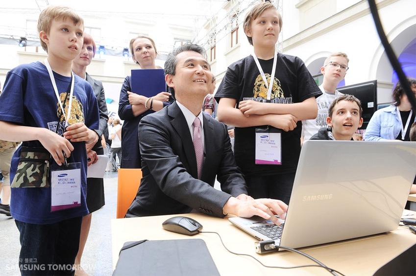 삼성 코딩 마스터 대회 폐회식 부스에서 삼성전자 글로벌 협력실 김상우 부사장이 아이들이 만든 코딩 프로그램을 직접 시행하고 있는 사진입니다