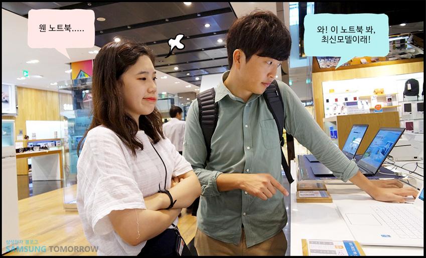 강남역 삼성 딜라이트샵에서 최신 전자기기를 구경하는 준수와 민화. 준수는 노트북을 바라보며 와 이 노트북 봐. 최신모델이야 라고 이야기하며 민화는 뾰루퉁한 표정으로 웬 노트북... 이라 이야기 하고 있습니다.