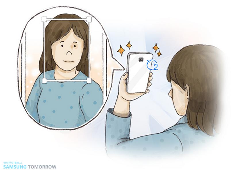 얼굴 자동 인식 기능으로 후면 카메라로 셀피를 찍는 모습을 그린 그림입니다.