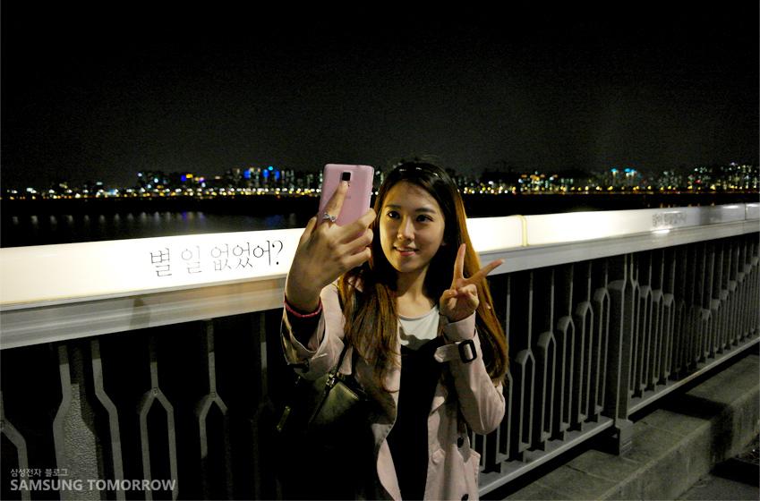 멋진 마포대교 야경을 배경으로 갤럭시 노트4로 셀피를 찍는 하한솔 학생 사진입니다