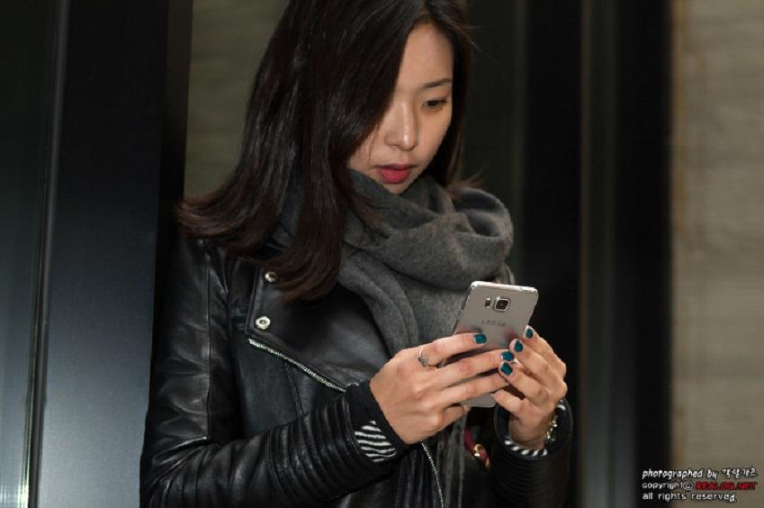 여성이 갤럭시 알파를 들고 있는 모습을 상반신만 촬영한 사진입니다.