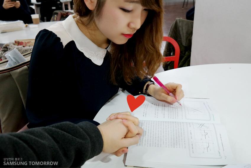 소영이가 오른손으로 남자친구의 손을 잡고 왼손으로 연필을 쥐고 공부하고 있는 모습입니다.