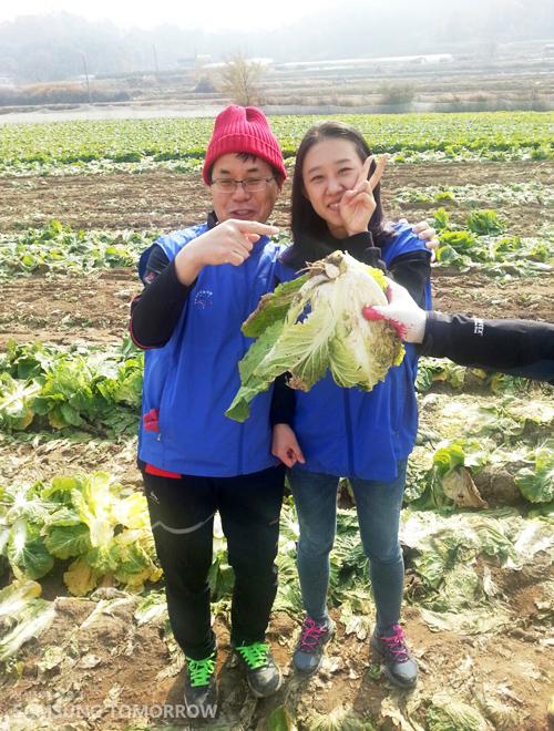 온양사업장 임직원들이 수확한 배추를 들고 웃고 있는 모습입니다.