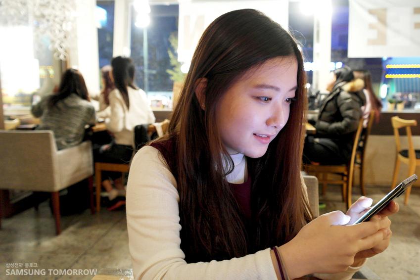 슬기가 웃는 얼굴로 스마트폰 화면을 보고 있는 모습입니다.