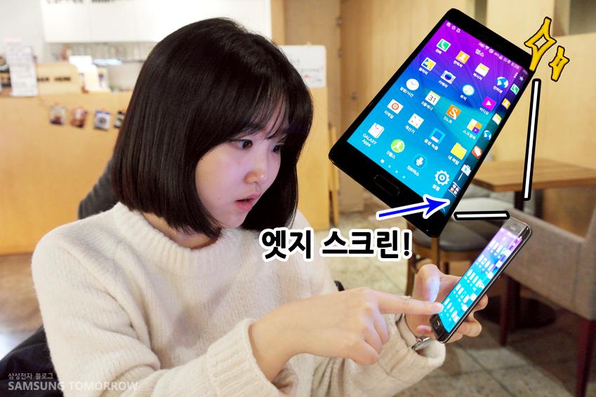 정현이 슬기의 스마트폰에서 엣지 스크린을 발견하고 놀라는 모습입니다.
