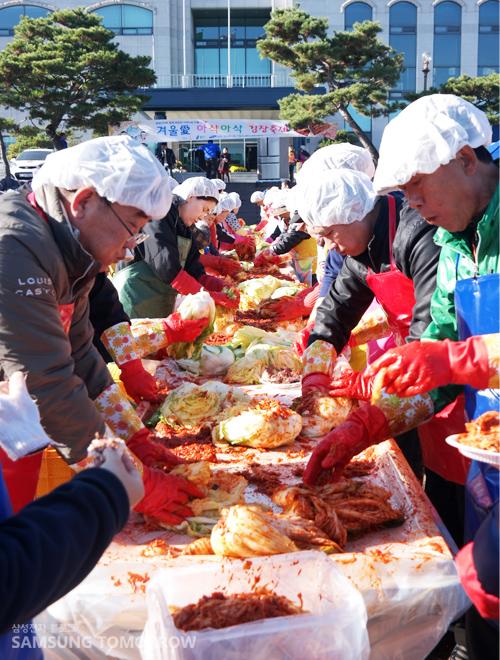 기흥화성사업장 임직원들이 겨울 김치를 담그기 위해 배추에 양념을 묻히고 있는 모습입니다.