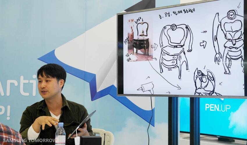 강사가 큰 화면에 예시 작품의 스케치를 보여주며 설명하고 있는 모습입니다.