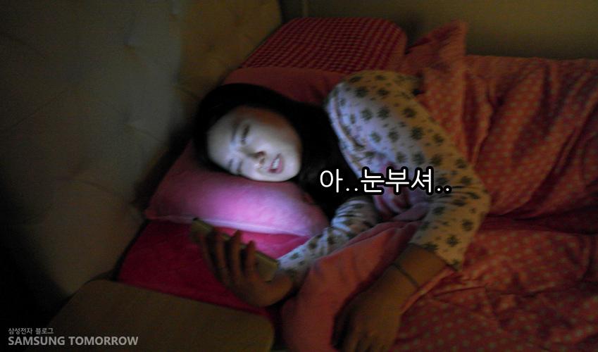 어두운 방에서 침대에 누워있는 여자가 스마트폰의 화면 불빛에 눈부셔하는 모습입니다.