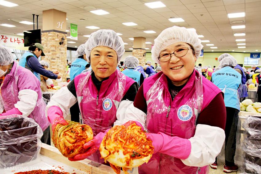 봉사자들이 자신들이 담근 김치를 내보이며 환하게 웃고 있는 모습입니다.