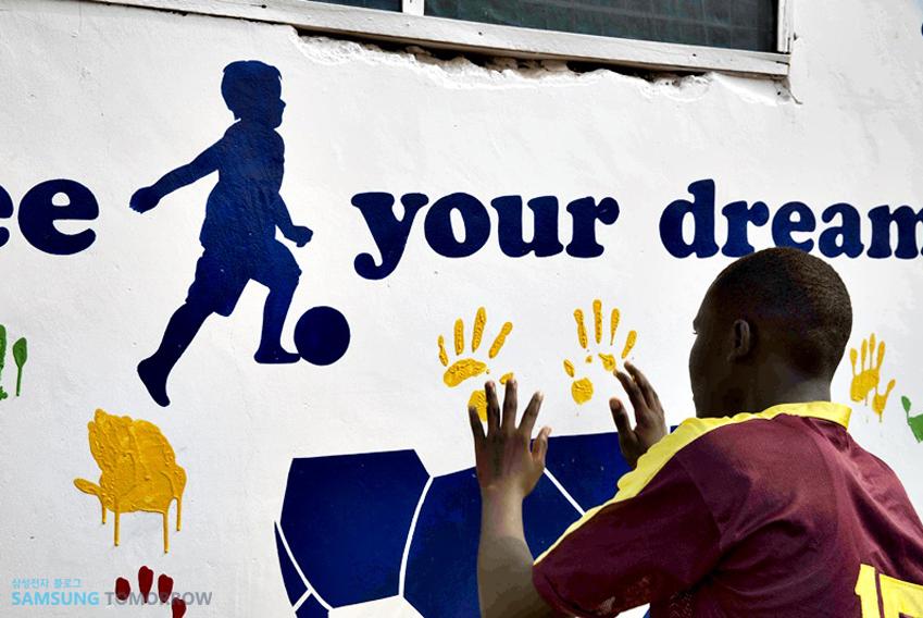 아프리카 소년이 벽화를 앞에 두고 손동작을 취하는 모습입니다