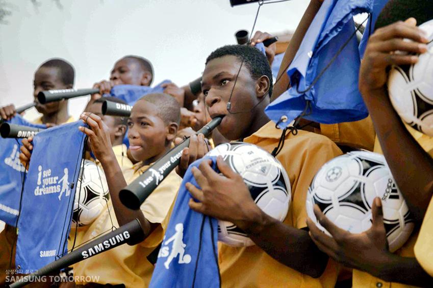 아프리카 유소년 축구팀이 삼성전자가 후원하는 축구공과 현수막, 응원용품을 들고 있는 모습입니다