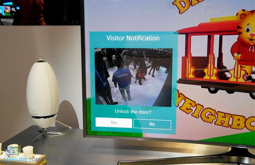현관에 설치된 카메라가 집 바깥 모습을 스마트TV로 보여주는 사진입니다