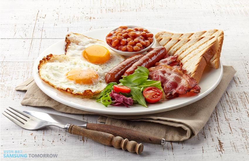 접시 위에 계란후라이와 소시지, 빵, 샐러드 등이 올려져 있습니다.