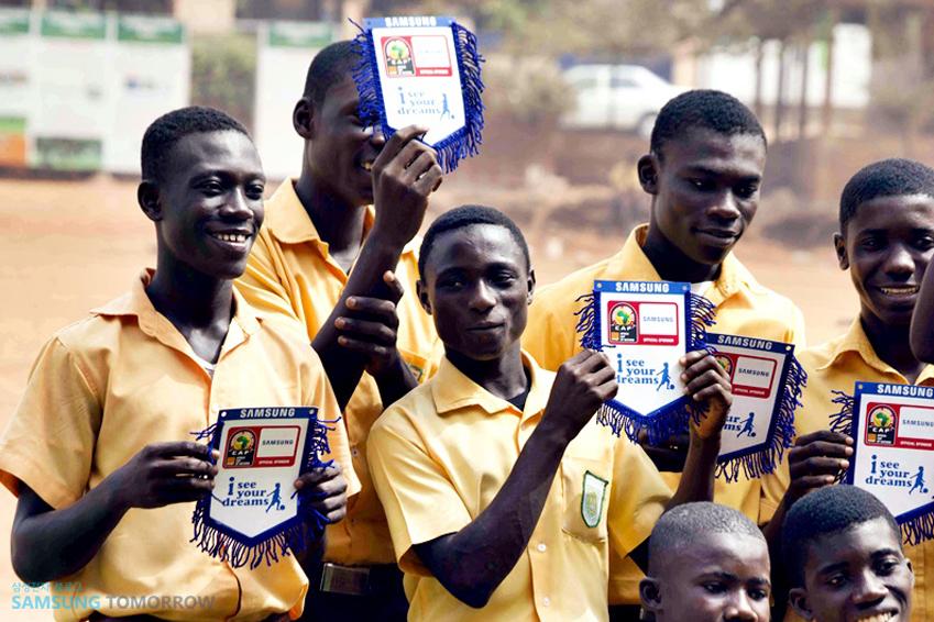 아프리카 유소년 축구팀이 아이 씨 유라고 적힌 종이를 들고 웃는 모습입니다