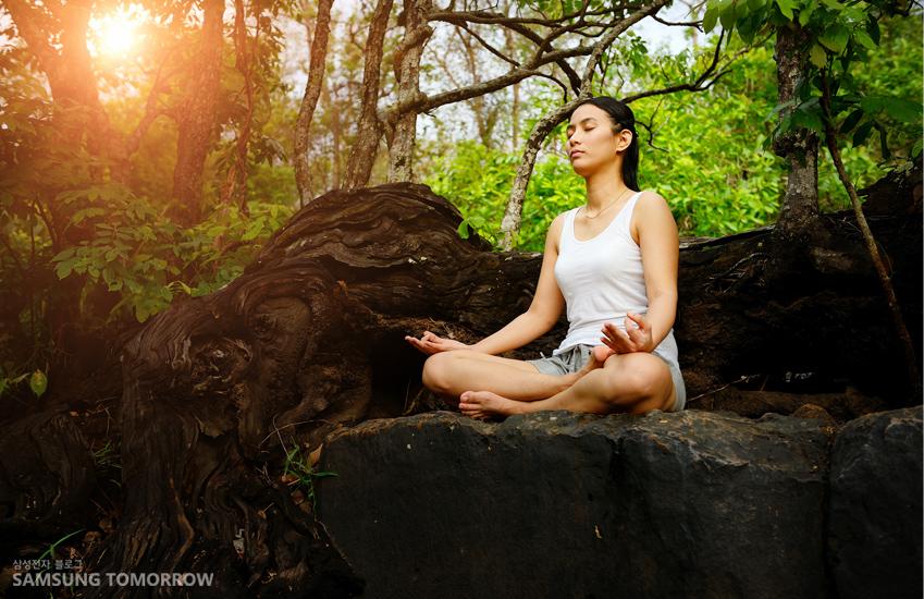 한 여성이 산속에서 가부좌를 틀고 앉아 명상하고 있습니다.