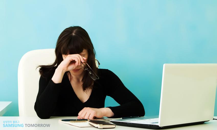 모니터 앞에서 눈 비비는 한 여성의 모습