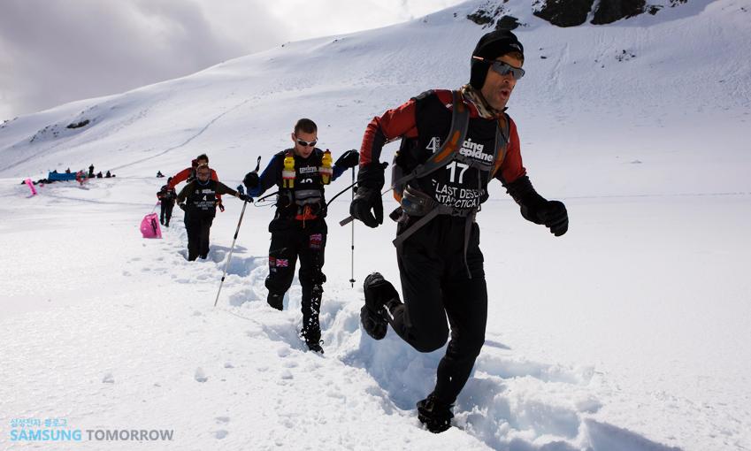 눈길을 걸어가며 스키를 즐기는 여행자들의 모습입니다.