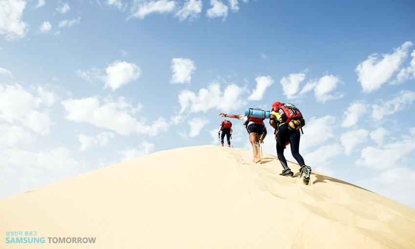 사막을 트래킹하는 여행자들의 모습입니다.