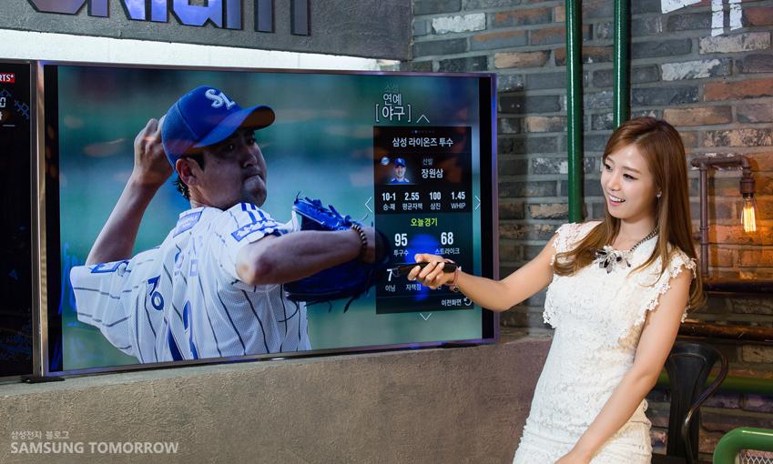 배지현 아나운서가 삼성 스마트 TV의 부가정보 서비스를 이용해 야구 중계를 보며 각종 야구 정보를 실시간으로 확인하고 있다