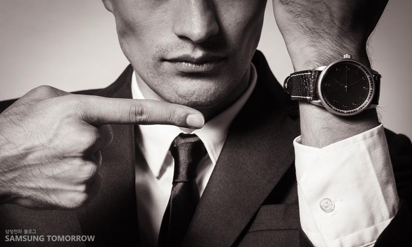 손목에 찬 시계를 가르키는 사진입니다.