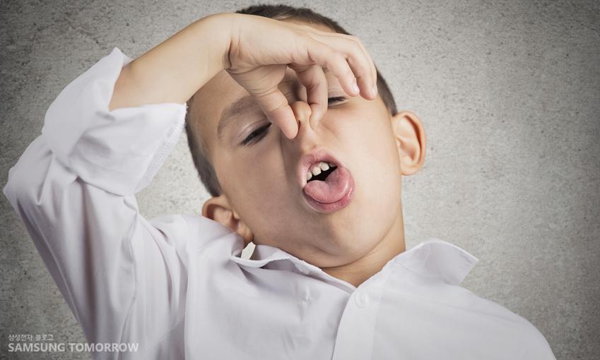 화장실 냄새에 코를 막고 있는 아이의 사진입니다.
