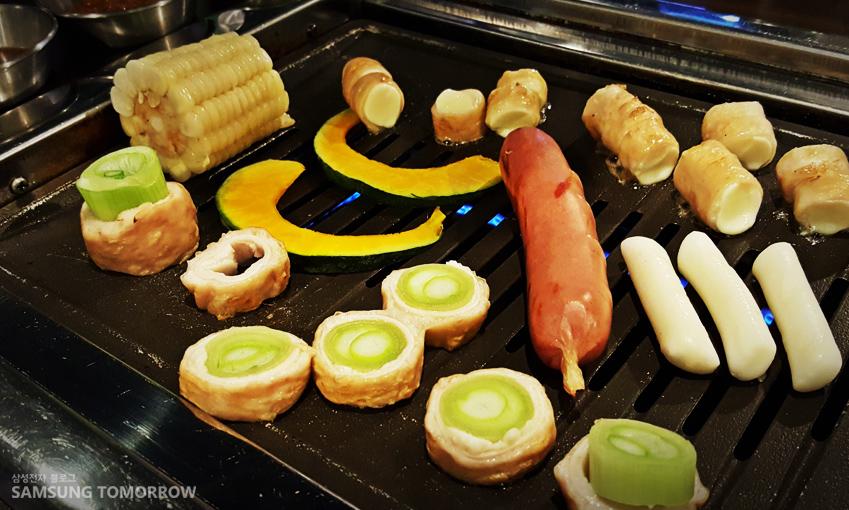 '치즈 막창구이'와 '대파 막창구이'가 다른 재료들과 불판에 있습니다.