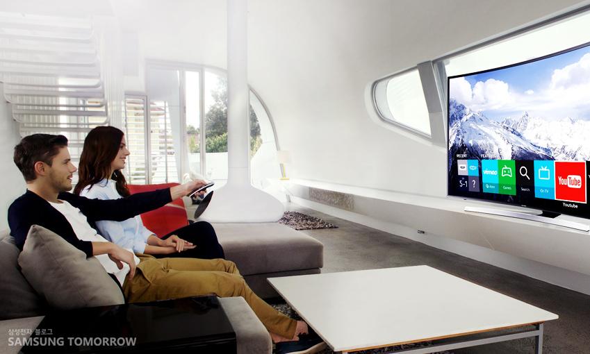 남녀가 쇼파에 앉아 티비를 보고 있습니다.