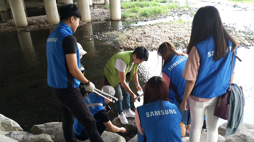 홍제천에서 환경 정리 봉사에 한창인 나눔VM 서울6팀 단원들