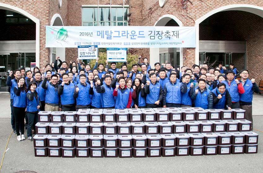 2016년 메탈 그라운드 김장축제 현수막 앞에서 삼성전자 한국총괄 임직원과 대한적십자사의 단체사진이다.