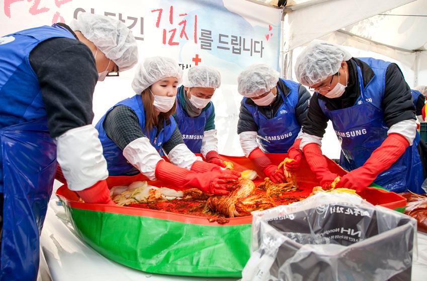 봉사자와 임직원들이 김치를 담고있는 모습이다.