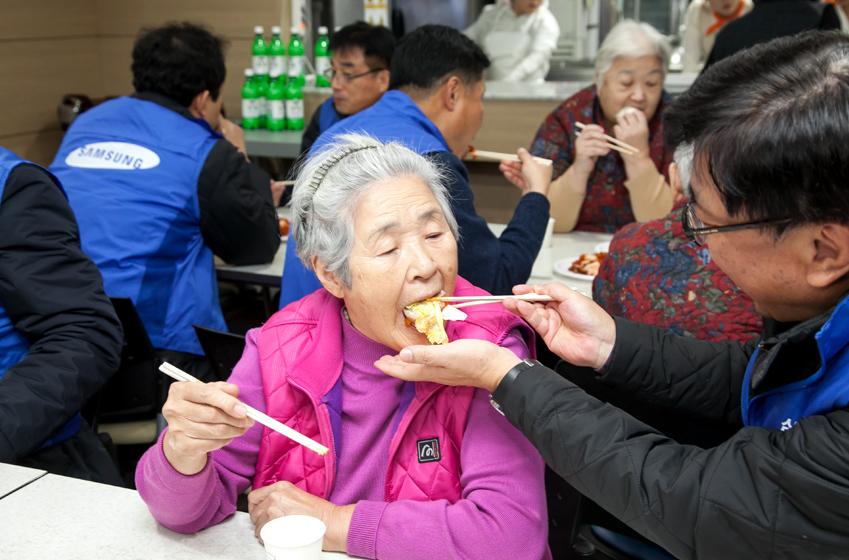 임직원이 할머님께 수육과 김치를 먹여드리고있는 모습이다