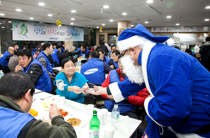 1일산타로 변한 임직원이 어르신에게 선물을 나눠주고있는 모습