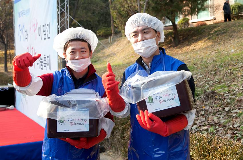 이원(사진 왼쪽) 대리와 박관희 대리가 김치통을 들고 웃으며 서있다.