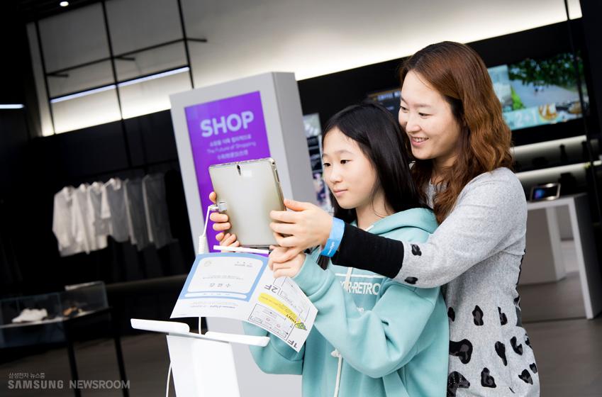 엄마와 딸이 리브 존에서 태블릿 기기를 사용해보고 있는 모습이다.