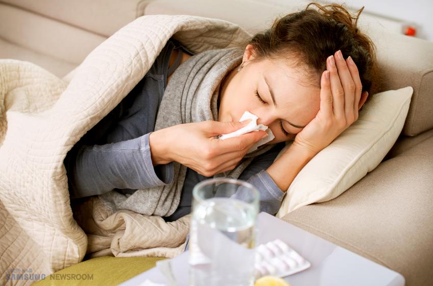 코를 풀고 있는 감기 걸린 여성