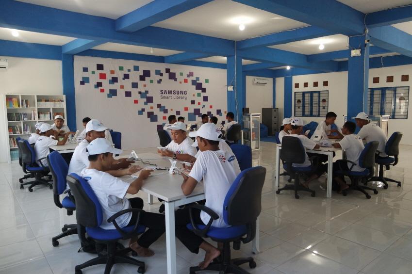 인도네시아 학생들이 모여서 각자 태블릿을 보고 있다