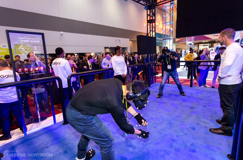 기어 VR과 손목 센서를 착용한 채 즐기는 4D 인터랙티브 게임을 즐기고 있는 2명의 관람객