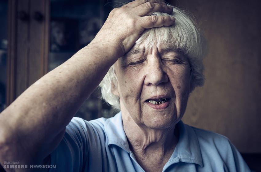 머리에 손을 대고 있는 할머니 모습