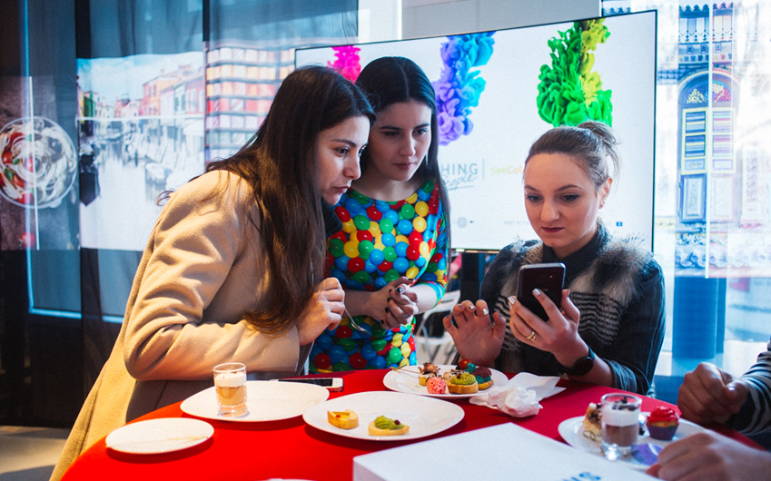 행사장을 찾은 관람객들은 #씨컬러스 앱을 통해 자신의 색각 이상 정도를 측정하고 보정된 화면을 제공 받았습니다 세 사람이 스마트폰을 보고 있다