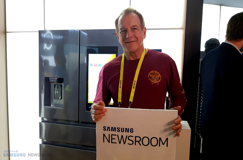 에릭 스미스(Eric smitt, 67) SAMSUNG NEWSROOM 플랜카드를 들고 웃고 있다