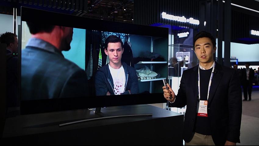 삼성 QLED TV 앞에 한 남성이 리모컨을 들고 무언가를 말 하고 있다