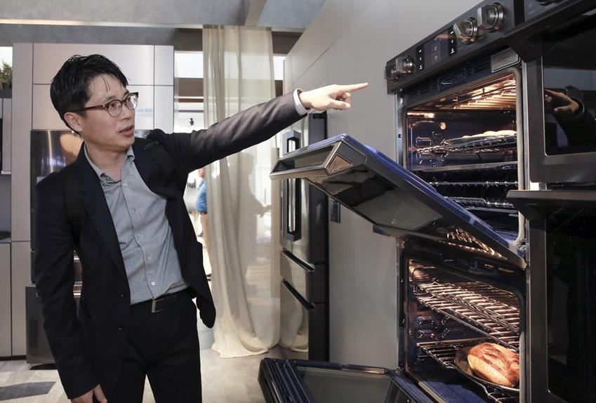 빌트인키친 부스 기획, 운영 작업에 참여한 김용완씨가 오븐을 가리키며 무언가를 말 하고 있다