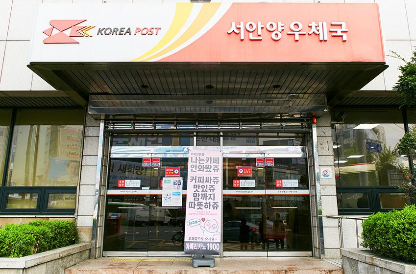 나는카페 서안양점이 위치한 곳은 서안양우체국(경기도 안양시 만안구). 나는카페의 커피를 광고하는 배너가 서안양우체국 입구 가운데 놓여져 있다.