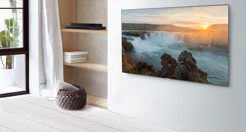 삼성 QLED TV가 벽걸이 형태로 거실 벽면에 붙어있다