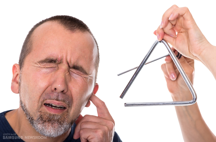 트라이앵글 소리에 귀를 막는 남성